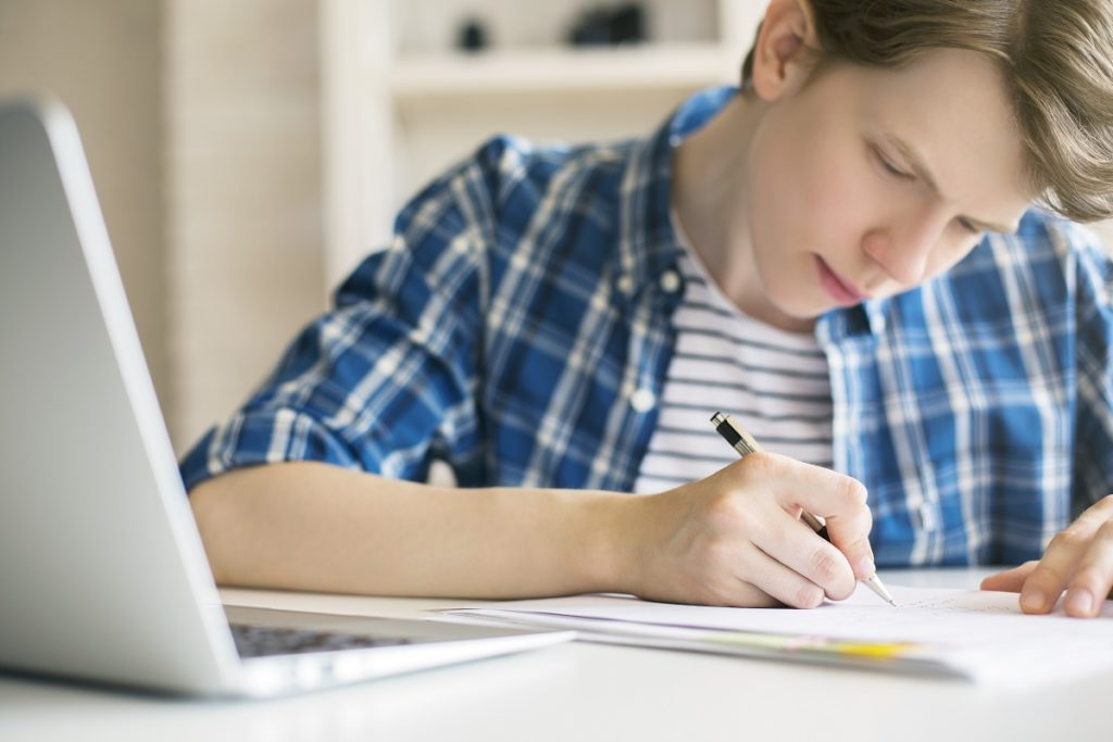 Boy writing on paper with his laptop open