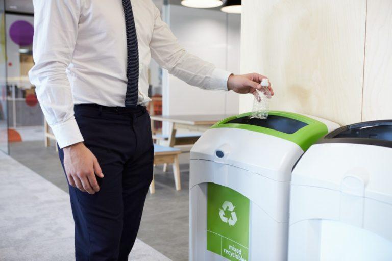 business man throwing plastic bottle in recycle bin