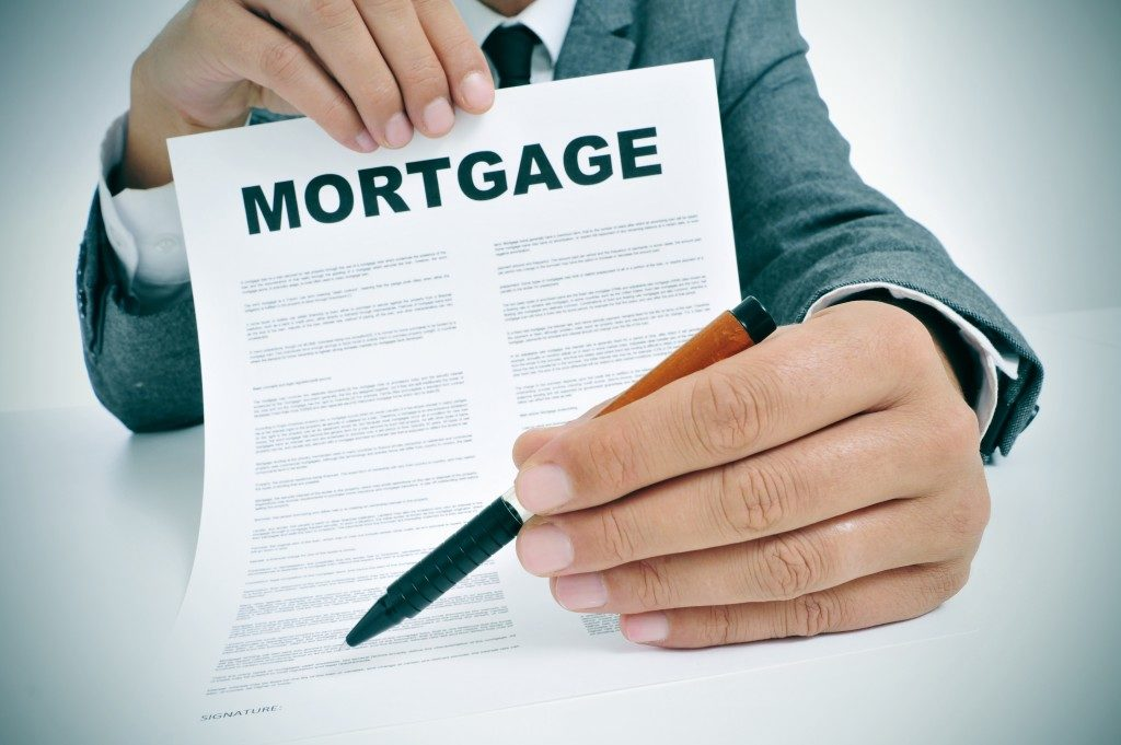 man wearing a suit showing a mortgage loan contract and handing the pen