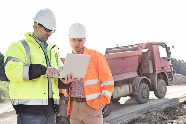 contractors holding laptop at a construction site