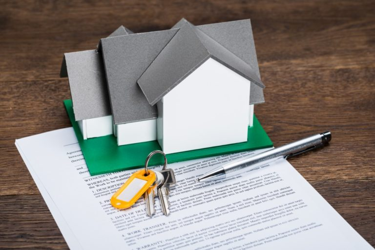 mortgage contract with house model and keys