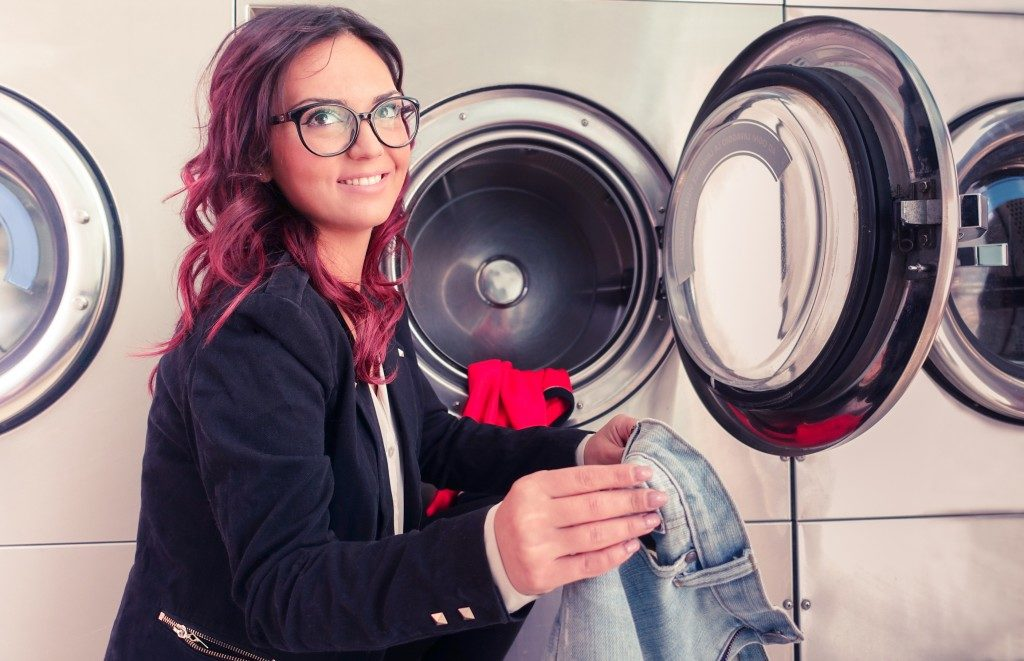 woman doing laundry in laundromat shop