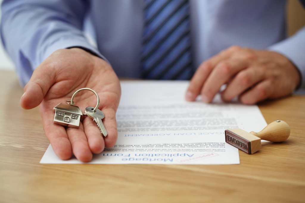 realtor handing the key of a home