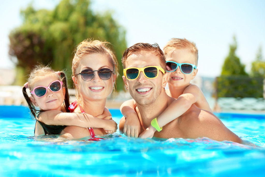 Family in pool wearing sunglasses