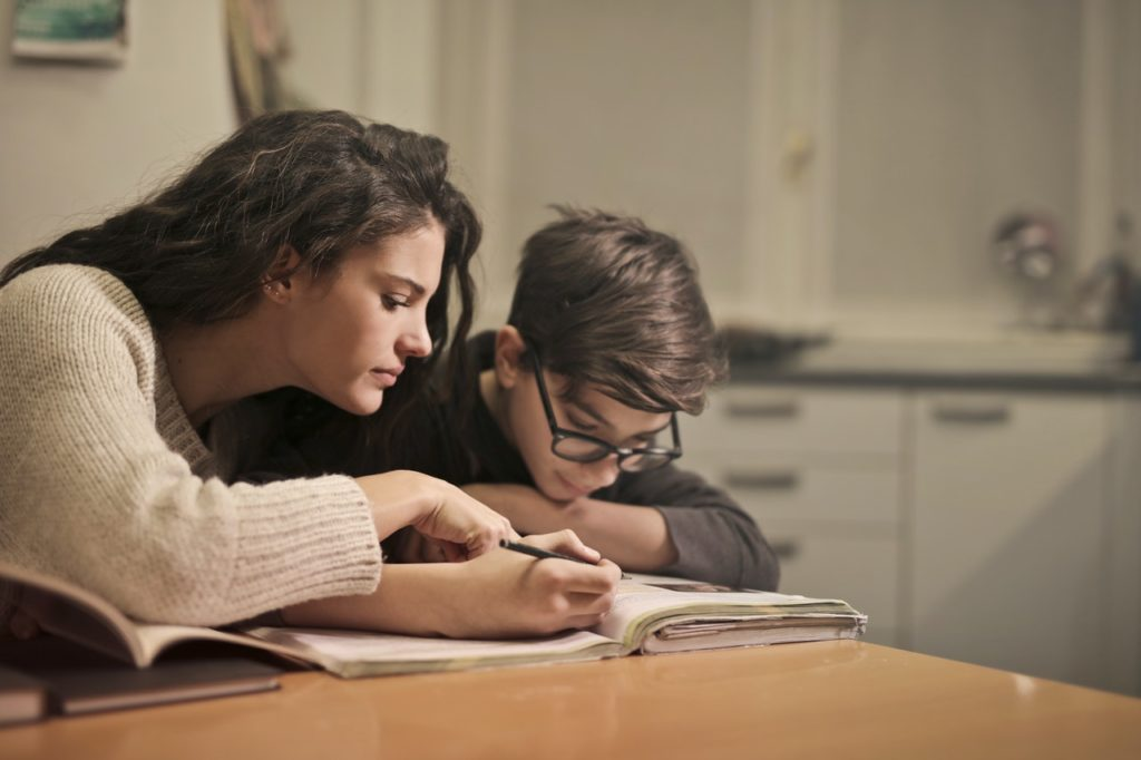 woman home schooling young boy