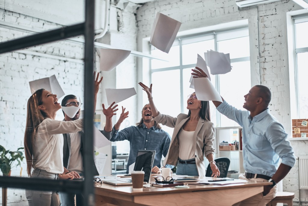 employees throwing paper into the air