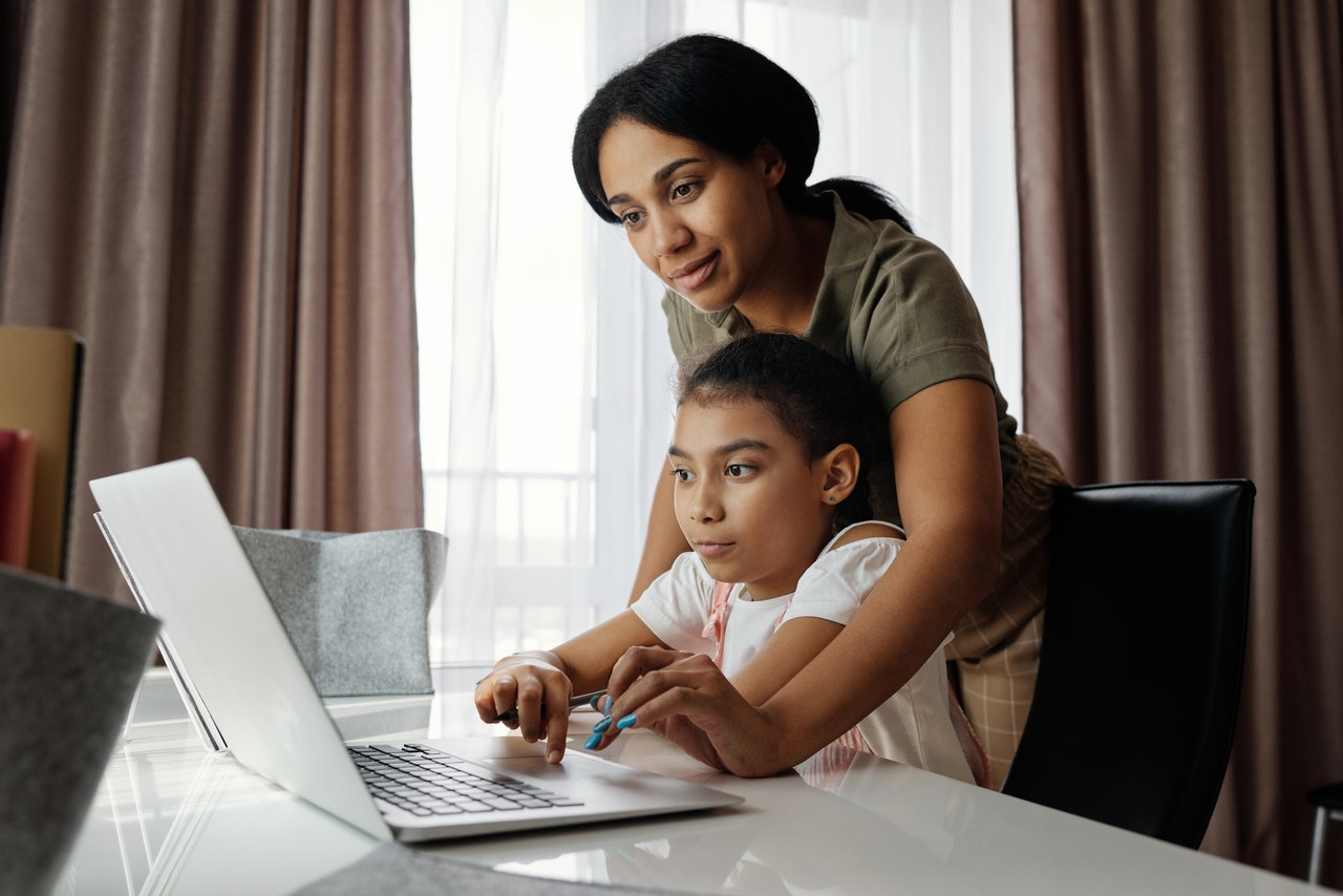mother helping her child on her online class