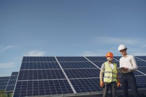 two people standing in front of some solar panels