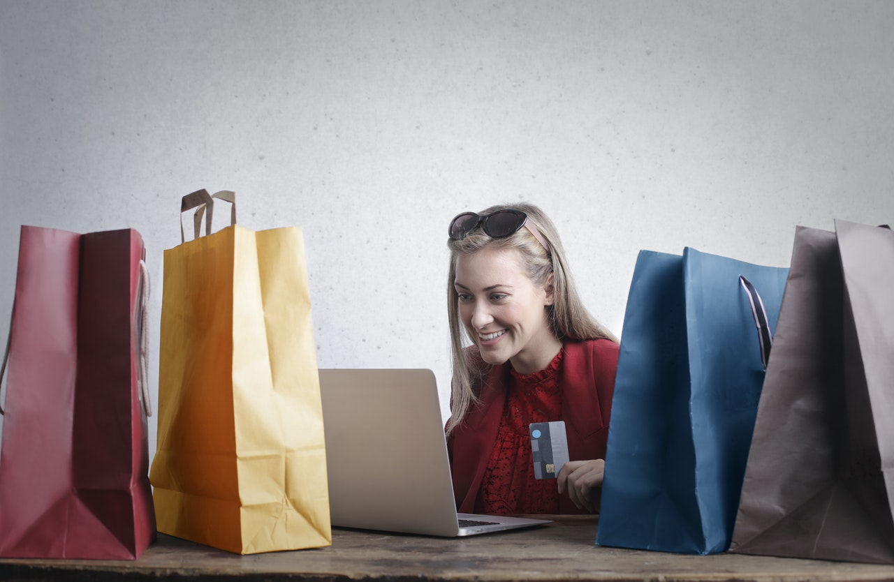 woman using her computer surrounded by paper bags