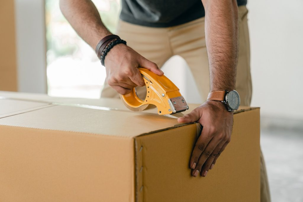 man sealing a box with packaging tape