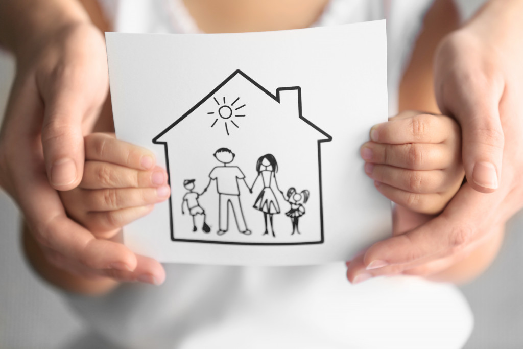 a child holding a piece of paper with an illustration of a house and family on it